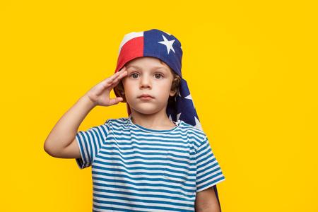 Boy giving salute on orange