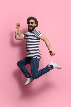 Stylish man jumping on pink