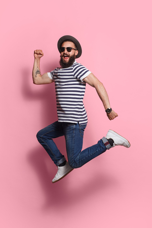 Stylish man jumping on pink