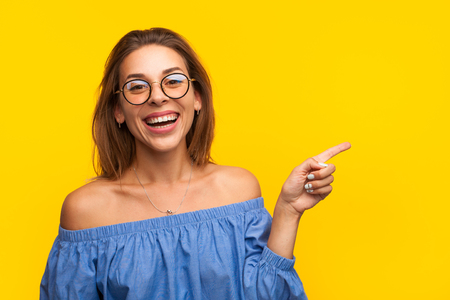 Cheerful model pointing away Stock Photo