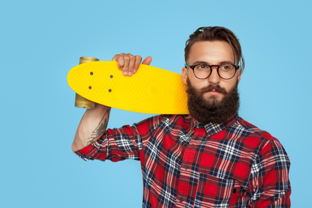 Confident hipster with yellow longboard