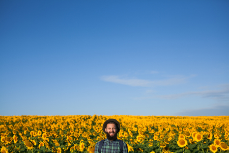 Smiling traveler in sunflowers field Stock Photo