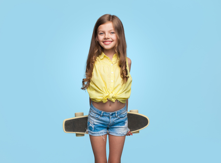 Cheerful girl with longboard on blue