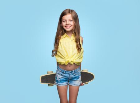 Chica alegre con longboard en azul Foto de archivo - 89044984
