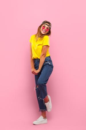 Charming hipster girl posing on pink