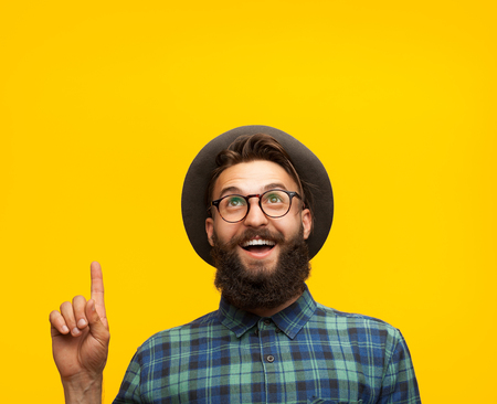 Content man pointing up on orange Stock Photo