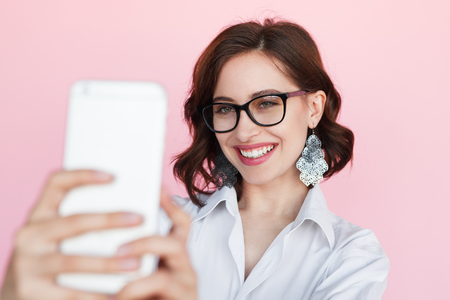 Smiling brunette woman taking selfie