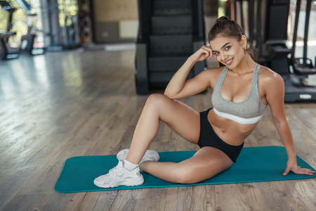 Woman in sportswear on stretching mat