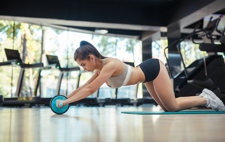 Woman with ab wheel Stock Photo