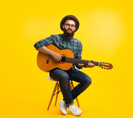 スタジオでギターを持った若い男 写真素材