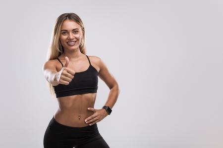 Woman in sportswear gesturing thumb up Stock Photo