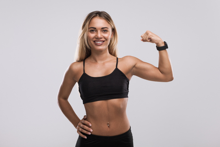 Smiling fit woman showing bicep 스톡 콘텐츠