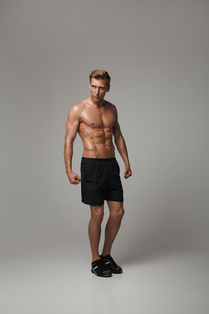 Muscular confident sportsman posing in studio