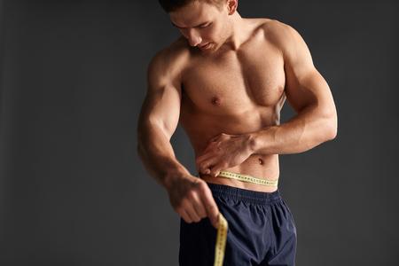 ウエストを測定する筋肉の男