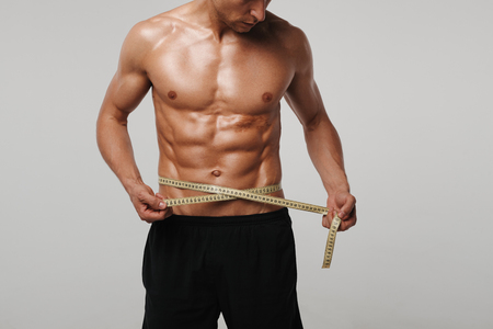 Man measuring his waist Stock Photo