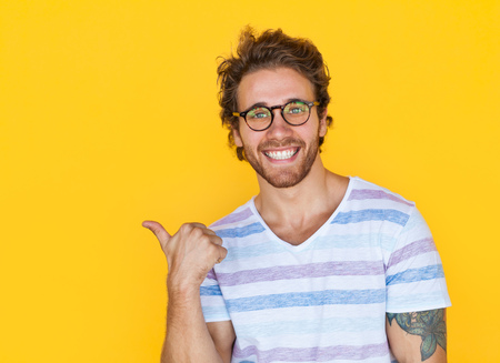 Smiling man pointing with thumb Stock Photo
