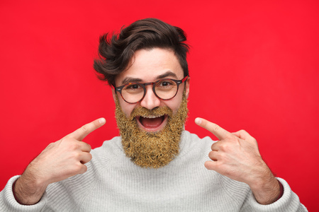 Handsome man with gold beard on red