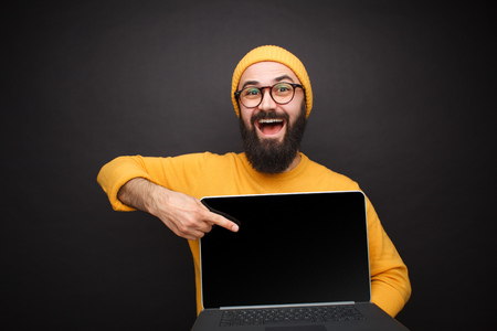 Smiling man pointing at laptop
