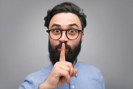 Bearded man gesturing silence