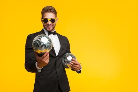 Jonge man in pak met discoballen Stockfoto
