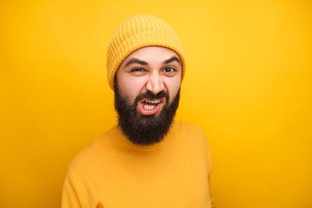 Grimacing man in yellow looking at camera