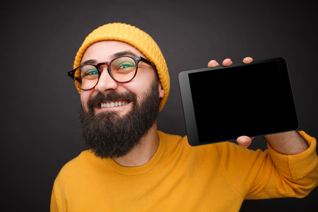 Content bearded man showing tablet