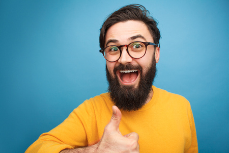 Excited trendy man showing thumb up Stockfoto