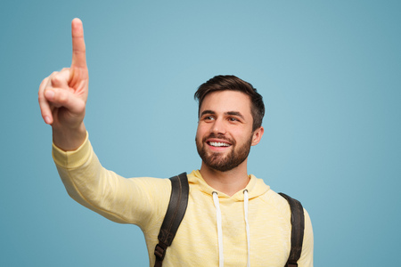 Smiling man indicating space with finger