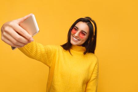 Charming hipster girl taking selfie
