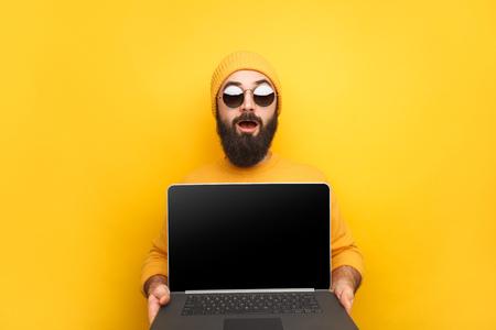 Trendy man advertising laptop 版權商用圖片 - 99231594