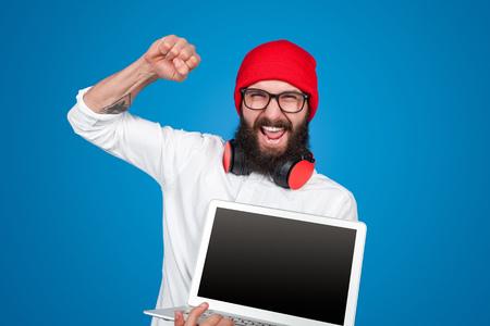 Trendy hipster promoting new laptop Banco de Imagens