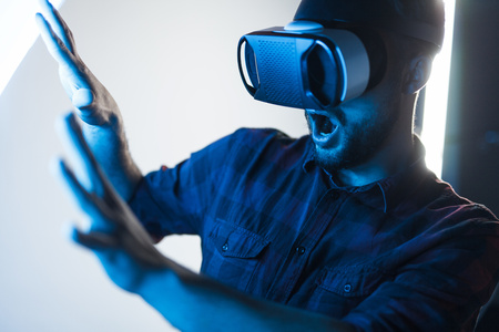 Scared guy in VR glasses exploring cyberspace Stock Photo