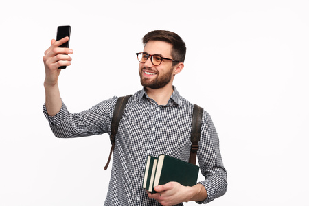 Confident man with books taking selfie