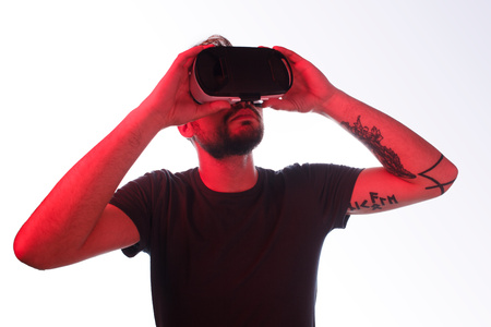 Casual man in VR glasses on white