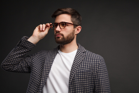 Classy male in glasses on gray