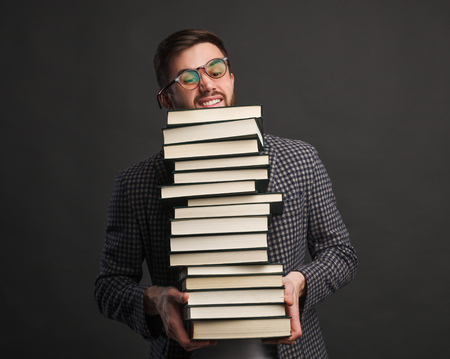 Exhausted student with big stack of books Imagens