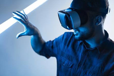 Amazed man in VR touching light