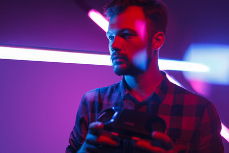 Young man holding VR glasses in neon Stock Photo