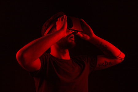 Amazed man exploring virtual reality in darkness