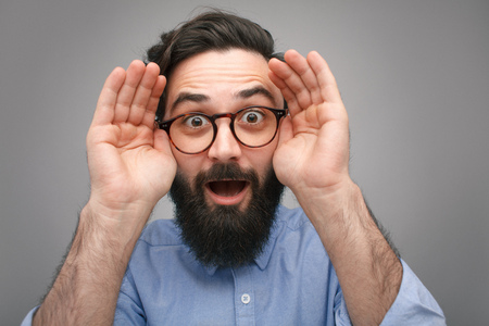 Expressive man revealing eyes in surprise Stock Photo