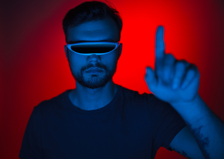Handsome young man wearing futuristic glasses and interacting with virtual reality options while standing on red background.  Imagens