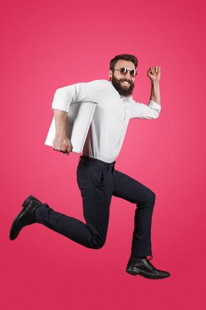 Stylish man running with laptop