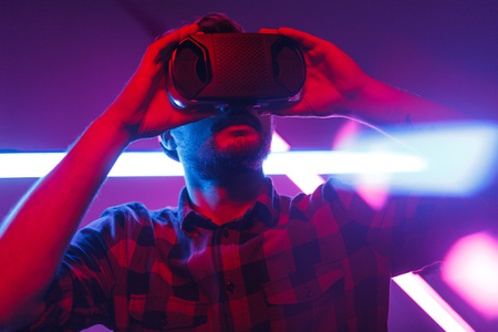 Casual man exploring virtual reality in neon