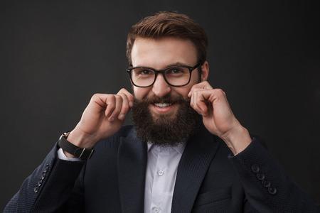 Cheerful elegant man curling mustache