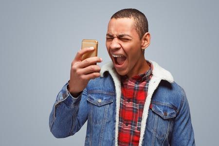 Angry man screaming at smartphone Archivio Fotografico - 103297465