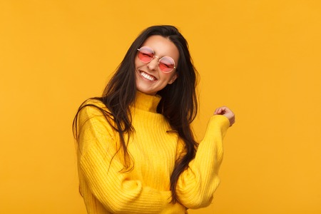 Stylish expressive brunette on yellow