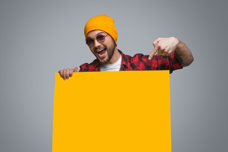 Trendy man pointing at yellow poster