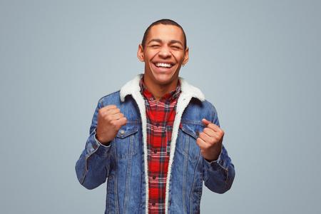 Cheerful black guy celebrating victory Reklamní fotografie