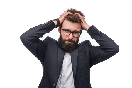 Man in suit with hands on head in studio