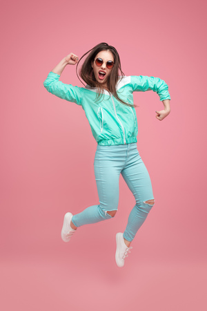 Expressive hipster woman jumping up